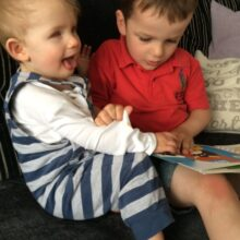 Alife and his brother Harrison reading together on the sofa.