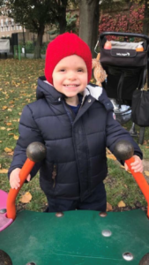 George wearing a hat and coat while at a park play area.