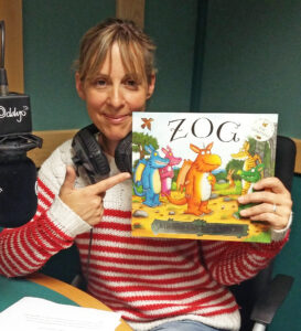 Mel ins tudio with headphones around her neck, holding up a book copy of Zog and smiling.