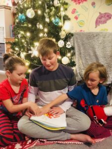 Three children in front of a Christmas tree feeling a tactile image of Zog