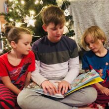 Three children sat in front of a Christmas tree reading an accesible, tactile and audio version of Zog