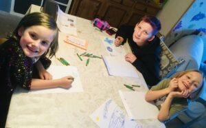Three children sat at a table drawing with crayons and smiling.