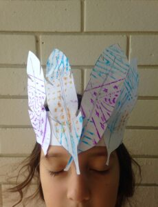 A girl with closed eyes wears a paper crown with crayon rubbings on.