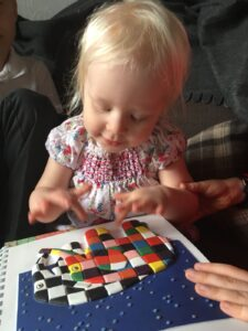 Matilda feeling a tactile image of Elmer and Wilbur