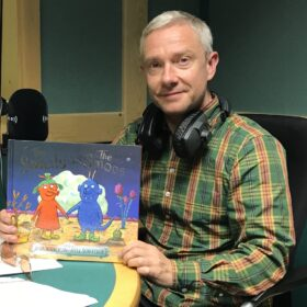 Martin Freeman sitting in studio, smiling, and holding The Smeds and The Smoos book.