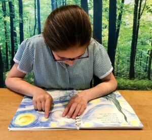 Imogen reading braille in Laurence Anholt's picture book, 'The Magical Garden of Claude Monet', available in part thanks to Children in Need.
