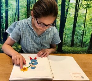 Imogen feeling a tactile picture from Laurence Anholt's picture book, 'The Magical Garden of Claude Monet' available in part thanks to Children in Need funding.