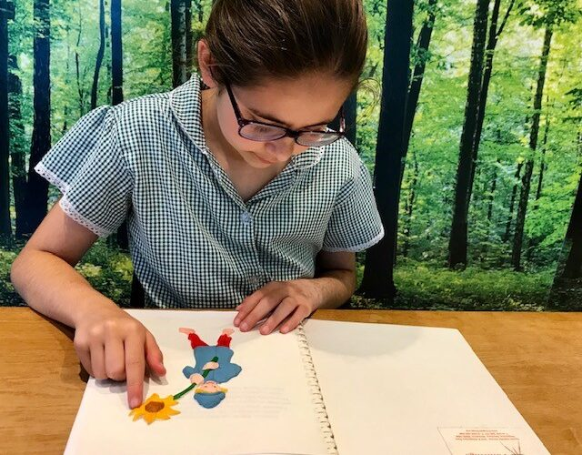 Imogen feeling a tactile picture from Laurence Anholt's picture book, 'The Magical Garden of Claude Monet'