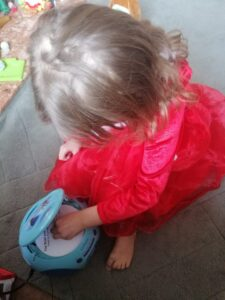 A young library member, Zannah, putting the audio guide CD into her Frozen-themed CD player.