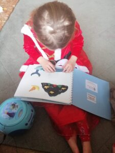 A young library member feeling a tactile picture of the whale from the book.
