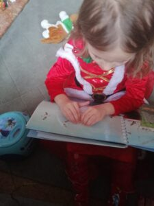 A young library member reading braille.