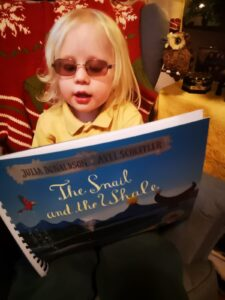 Matilda holding 'The Snail and the Whale' showing the front cover of the book to the camera.