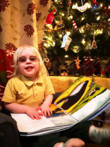 A young library member, Matilda, looking up at the camera as she feels the braille in the book. A Christmas tree is in the background.
