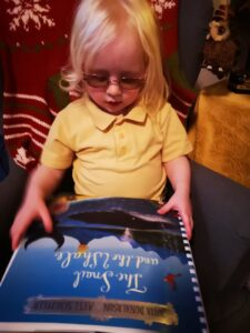 Matilda looking down at the front cover of the book.