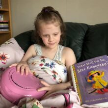 Library member Tayen sitting with her pink CD player and Touch to See copy of 'What Shall We Do, Blue Kangaroo'.