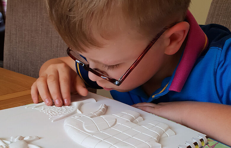 A close-up of a boy feeling a tactile picture.