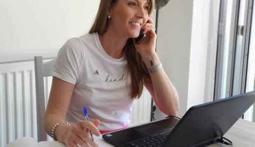 Librarian, smiling, on the phone with laptop open