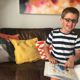 7-year-old Lucas smiling as he feels one of the tactile pictures in our Touch to See version of The Smeds and the Smoos