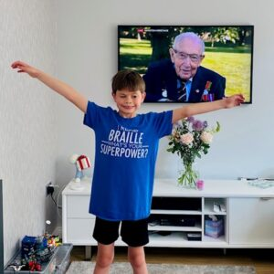 Ted smiling and standing jubilantly in front of his hero (on a TV screen) Captain Tom Moore.