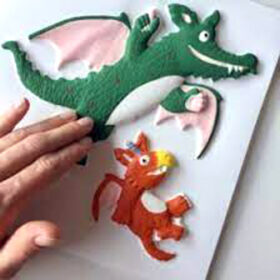 fingers touching a tactile image of Zog the orange dragon