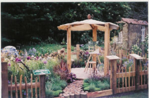 A rustic cottage garden. In the round decked area in the centre there is a solitary easel with canvas and small wooden stool.