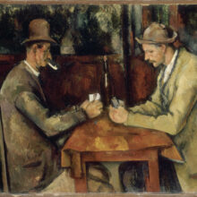 Two men seated across a small wooden table, deep in thought as they play cards.