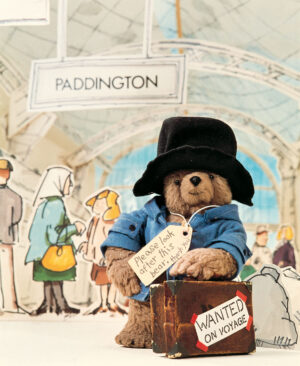 This famous little bear, in is blue duffle coat and black felt hat, stands stands leaning on his battered brown suitcase at Paddington Station.