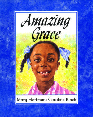 Amazing Grace written by Mary Hoffman and illustrated by Caroline Binch. A smiling black girl wearing a pink chequered shirt and with her hair in plaited pig tails with blue ribbons.