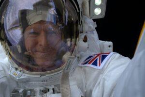 Selfie photograph of Tim Peake in white spacesuit and helmet.