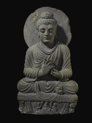 Stone sculpture of a Buddha seated on cushion, hands folded in prayer.