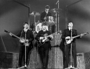 Iconic black and white photograph of The Beatles, Band, all four are playing guitars.