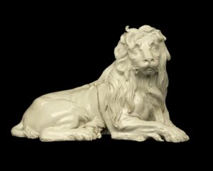 White porcelain lion laying down with its front legs crossed, its face has almost human features.