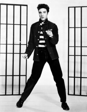Black and white photograph of a young Elvis Presley, dressed in black, dancing and singing.