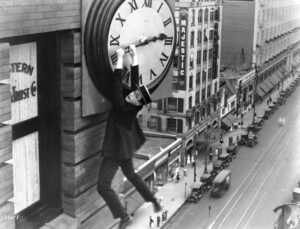Black and white photograph of a man in grey suit and boater hat clinging to the hands of a clock, high up on the sides of a tower block.
