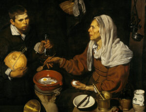 Old lady in peasants clothes bent over cooking eggs in a terracotta pot
