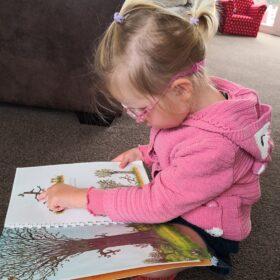 Little girl feeling the braille in Stick Man book.
