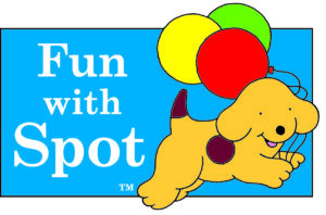 Fun With Spot. A yellow puppy with a brown spot on his side leaps in the air whilst holding a red, yellow and green balloon,