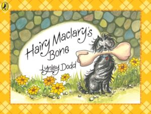 Hairy Maclary's Bone written and illustrated by Lynley Dodd. A black dog with long fluffy hair and a red collar sits obediently amongst pretty yellow flowers as he holds a very large bone in his mouth.