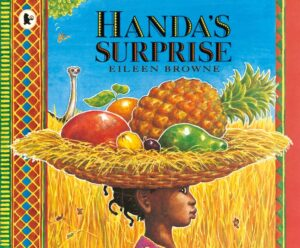 Handa's Suprise written and illustrated by Eilleen Browne. An african girl holds a wide, woven bowl on her head filled with fruit including a pineapple, mango, papaya, lemon and orange while peeping from behind is the long neck of an ostrich.