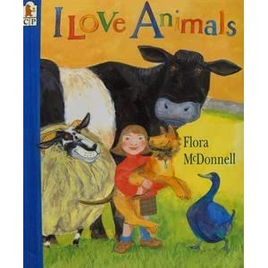 I Love Animals written and illustrated by Flora McDonnell. A smiling girl holds a large dog, surounded by farmyard animlas including a duck, cow and sheep.