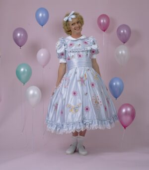 Man dressed up in white dress, surrounded by balloons.