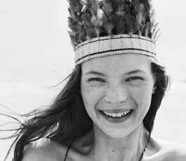 Black and white photograph of Kate Moss wearing a feathered headress.