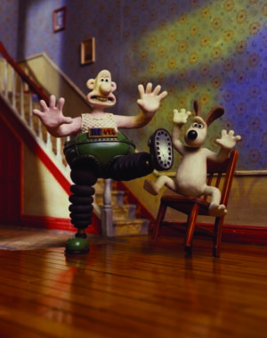 Plasticine characters Wallace and Gromit inside their house, Wallace wearing mechanical trousers and a rather shocked looking Gromit seated in a wooden chair.