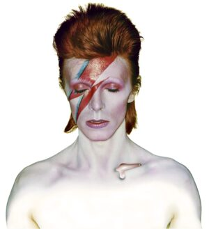 Iconic head and shoulder photo shot of David Bowie wearing heavy makeup including a dramatic bright red and blue thunderbolt across his face.