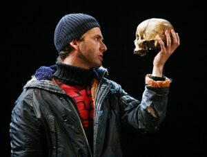 Head and shoulders photograph of David Tennant as Hamlet. In his right hand he holds a skull and is looking at it enquiringly.