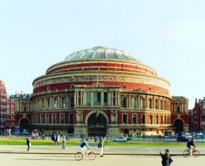 Photograph of the Royal Albert Hall, an imressive round building with a dome shaped roof.