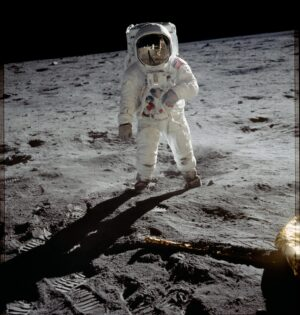 Photograph of Buzz Aldrin in full space suit walking on the surface of the Moon.