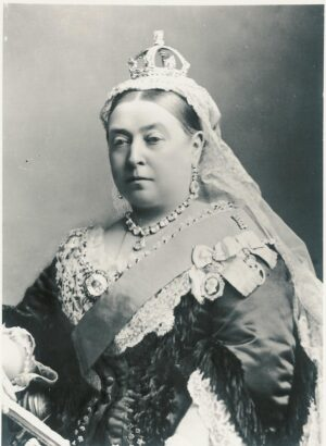 Queen Victoria seated wearing crown, white veil, diamond necklace and black embellished dress.