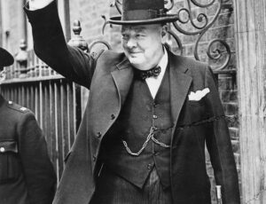 Sir Winston Churchill wearing black suit, bow tie and top hat, making his famous V for Victory sign with his right hand.