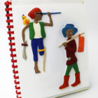 Two tactile pictures of Grace, as a pirate (with a parrot on her shoulder, sword, one leg and telescope) and Dick Whittington (wearing blue hat, red boots, carrying a stick with a bag on the end).